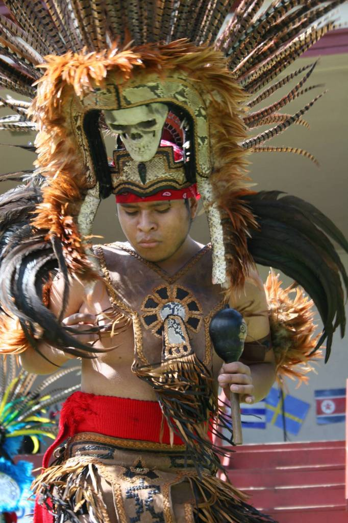An Aztec dancer, garbed in a symbolic headdress entertains the audience during International Market Day in Faribault.