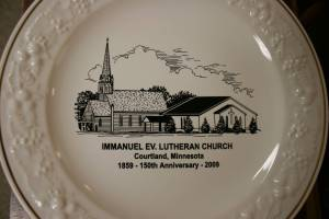 A commemorative plate shows the old and new Immanuel churches and celebrates the congregation's 150th anniversary.
