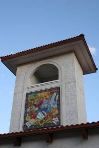 A colorful mosaic graces a building.