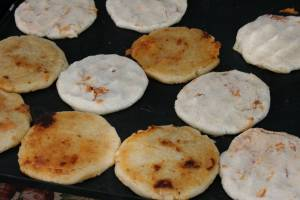Beef and cheese-filled pupusas fry on a griddle.