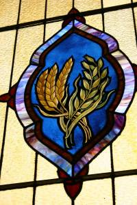 A side stained glass window features grain, reflecting the congregation's agricultural heritage.