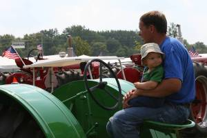 The look on this baby's face is so precious. And so is the loving way the child is held by his/her father, who is awaiting his spot in the tractor parade.