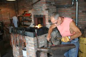 At work in the blacksmith shop, shaping metal.
