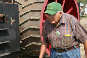 I like the determined look on this retired farmer's face as he passes a gigantic Rumely steam engine..