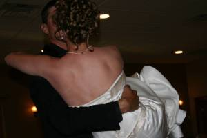 Corey carries his bride into the wedding reception.