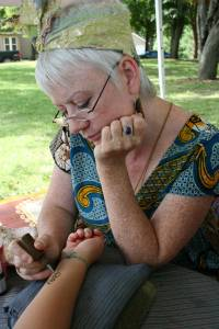 Judy Ostrowski applies henna art at Depot Park in Kenyon.