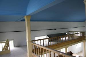 Inside the 1862 church, restoration continues, including work on the balcony area. The blue color is historically correct to the original church.
