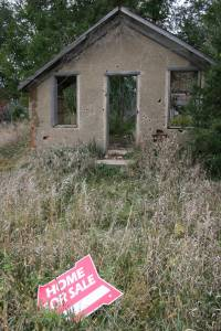 """The """"for sale"""" sign actually directs potential buyers to a house just down the road. But I thought the signs placement in front of this dilapidated school quite humorous."""
