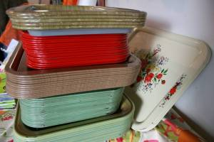 A stack of vintage trays awaits diners.