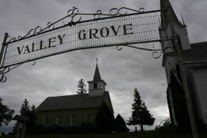 A sign marks the entry into the grounds of Valley Grove church with the 1862 church on the left and the 1894 church on the right.