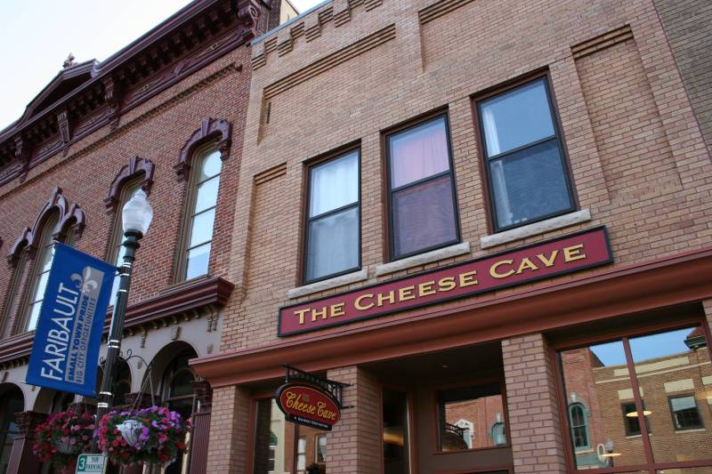 The Cheese Cave is housed in a beautifully-restored building in historic downtown Faribault. The interior, with an arched ceiling and sandstone-colored walls, mimics the caves where Faribault Dairy ages its cheeses.