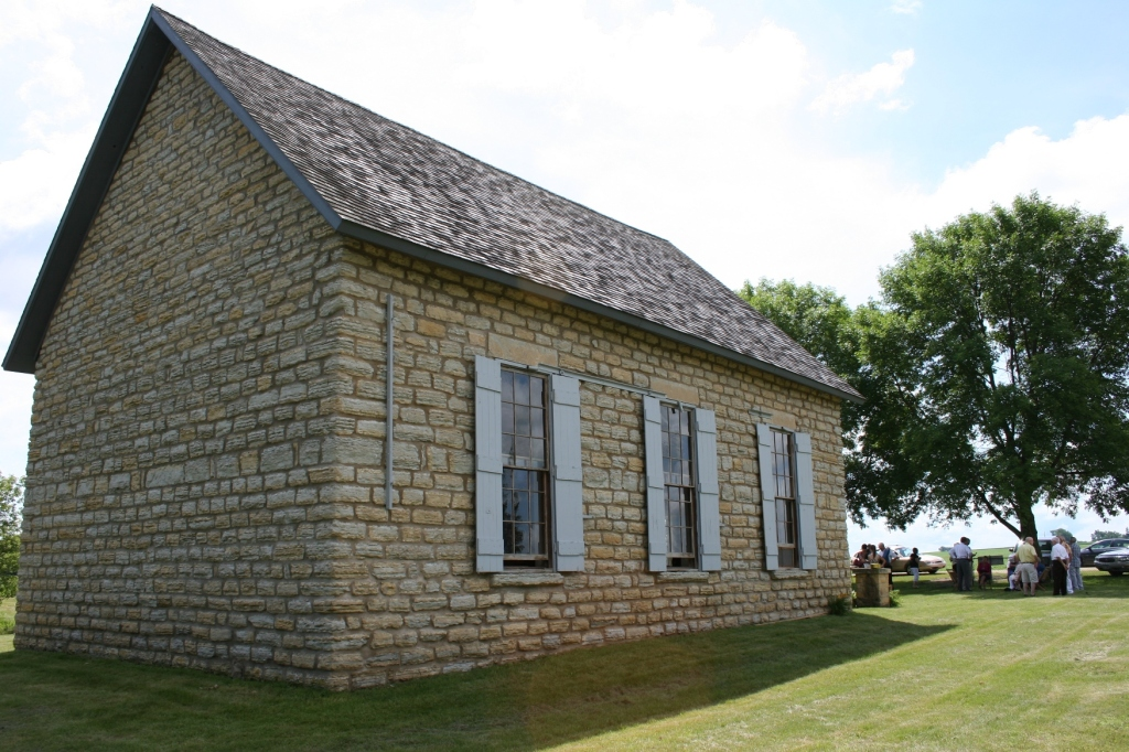 A rear view of the Old Stone Church, a simple structure with three shuttered windows running along each side of the building.