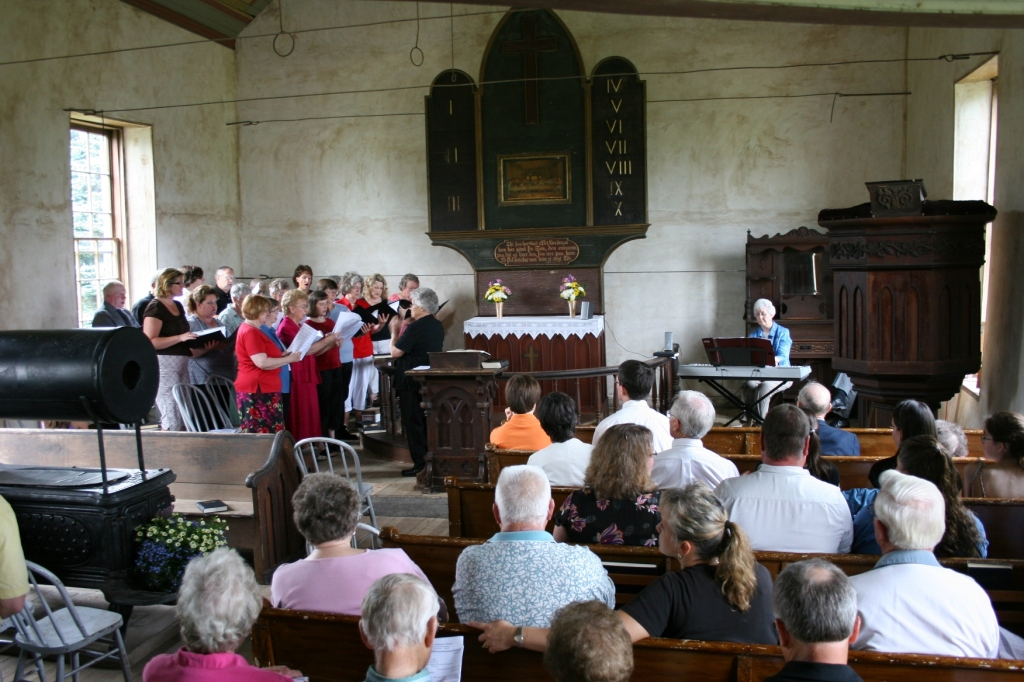 """During a worship service filled with music, choir and congregational members sing in Norwegian, """"Ja, vi elsker."""""""