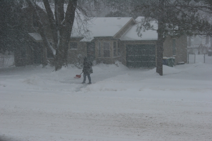 My neighbor across the street shovels snow Saturday morning.