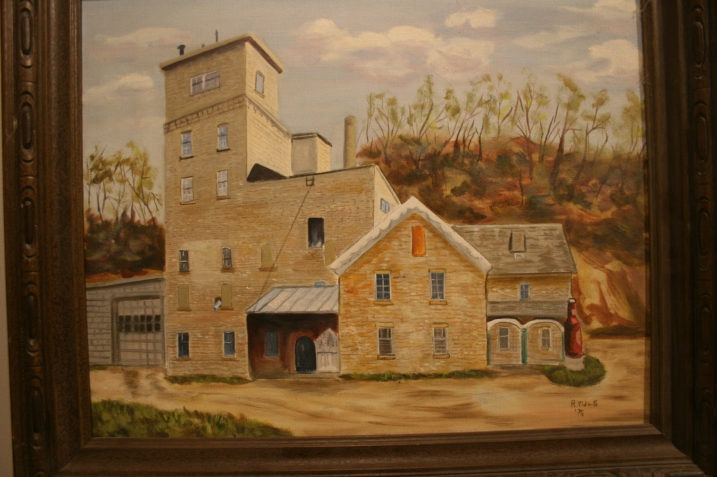 Faribault artist Rhody Yule created this oil painting of the Fleckenstein Brewery in 1976. The building, and the brewery, no longer exist. The 20-foot Fleck's beer bottle on the right side of the painting sat near the brewery entrance. Children often had their pictures taken here when their parents took a brewery tour.