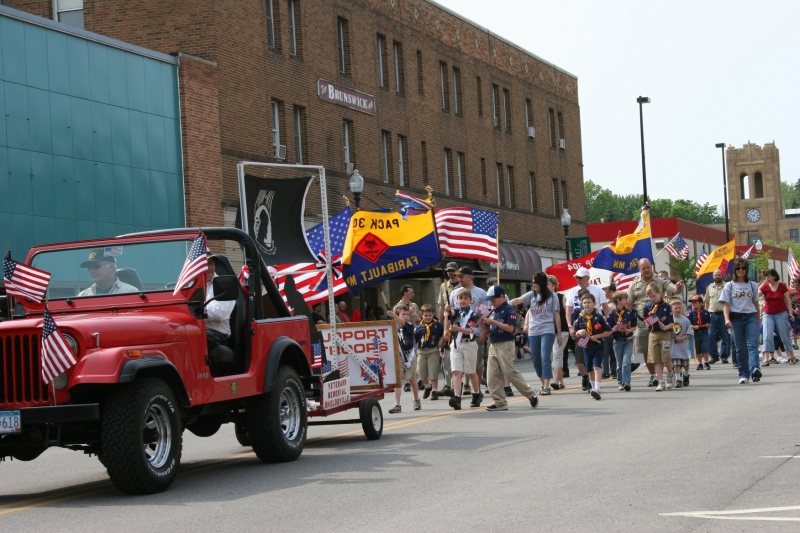 Boy Scouts march down Faribault's Central Avenue, giving away small American flags, during Monday's Memorial Day parade.