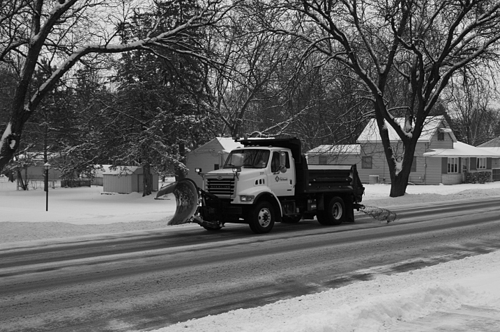 A city of Faribault snow plow spreading salt and sand onto the street past my house on Monday.