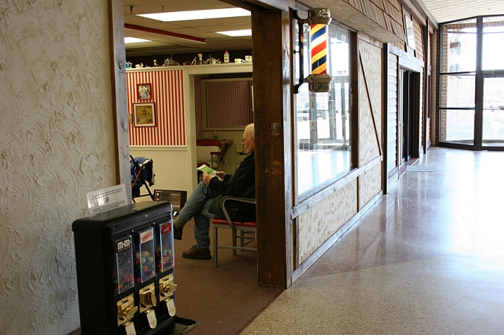 Reading a newspaper while waiting at the mall barbershop.