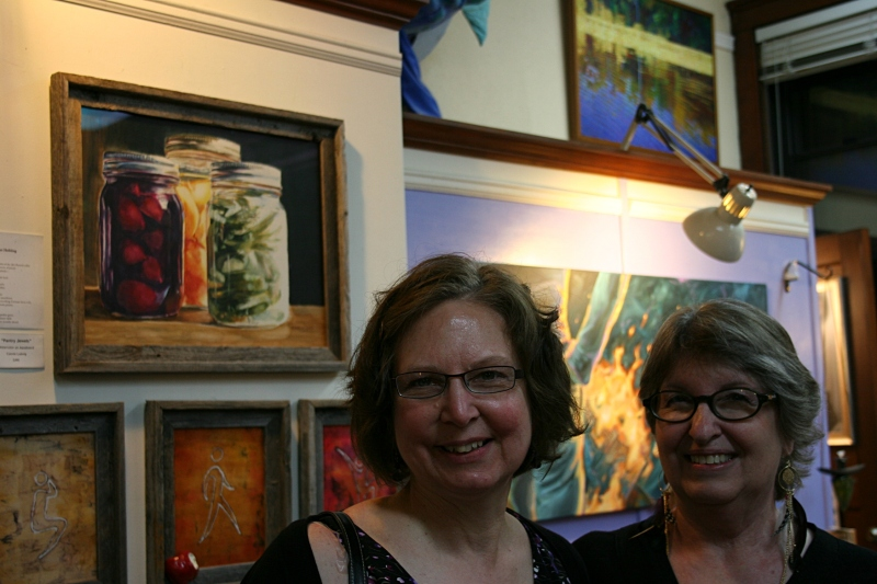 "Connie, right, and I posed for a photo after a 90-minute presentation in which poets read their poems and artists talked about how their art was inspired by the poem. Note Connie's ""Pantry Jewels"" painting just above my head to the left. If I could buy this $490 watercolor on aqua board, I would in a snap."