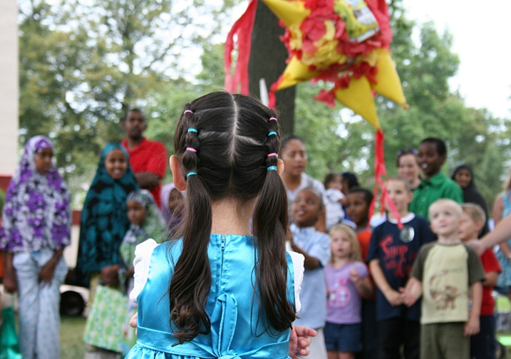 A little girl stands on the opposite side of the group of children waiting to swing at the pinata.