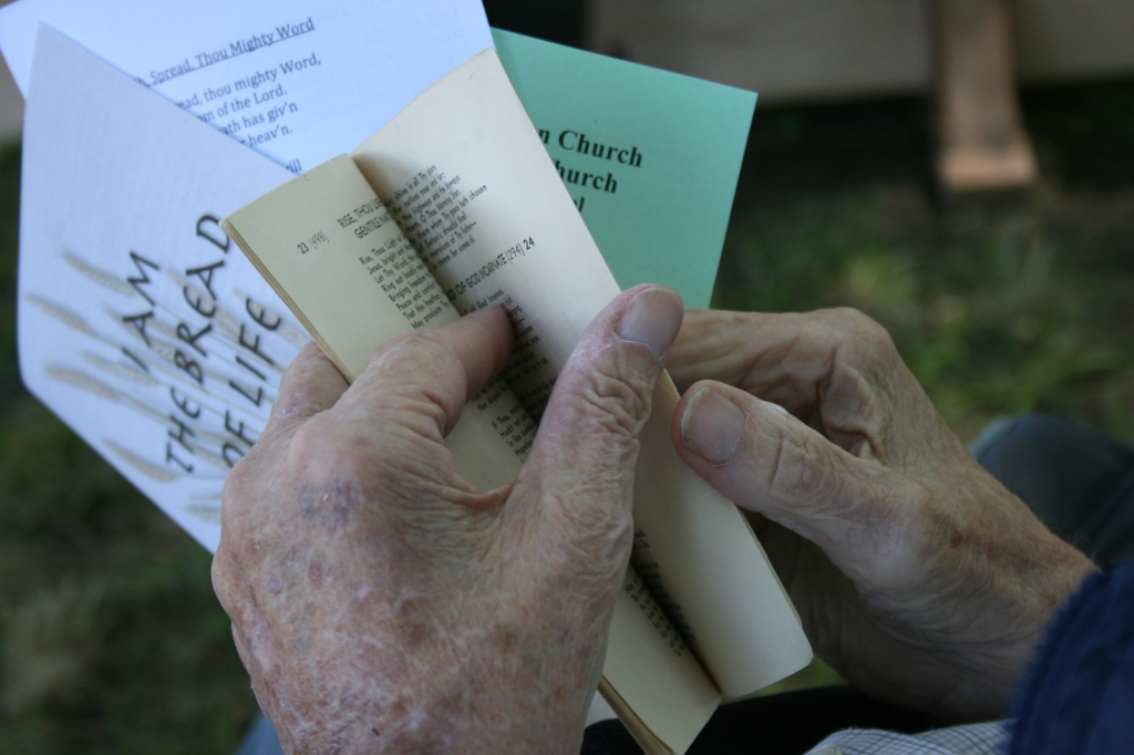 An elderly man turns to a hymn in the old pocket-size songbook that's been used for decades.