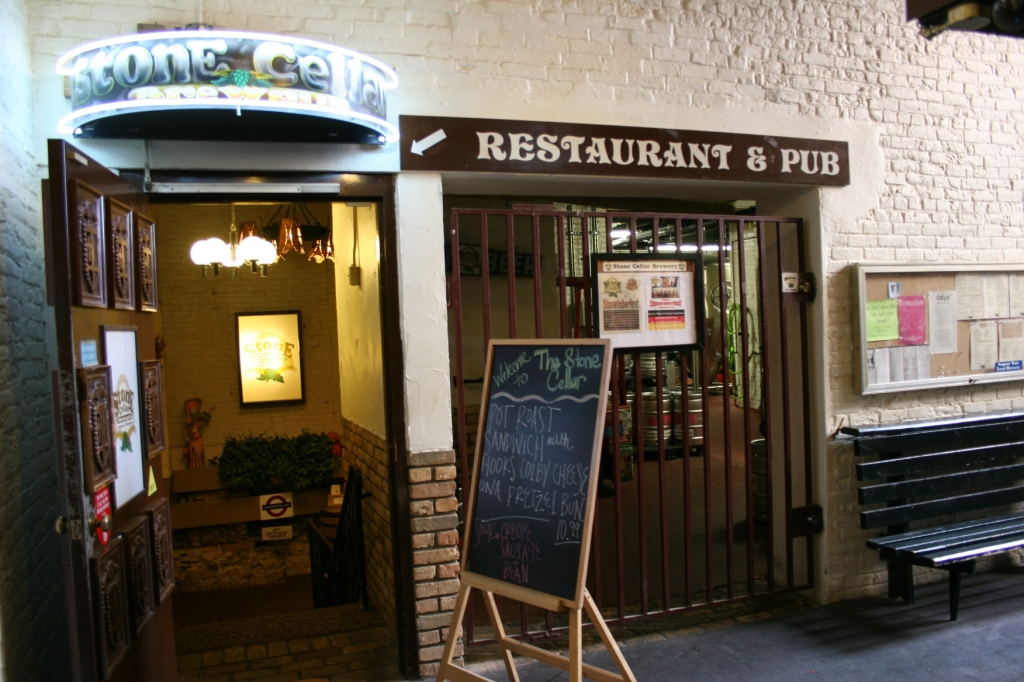 Go through the doorway on the left and follow the steps down into the Stone Cellar Brewpub.