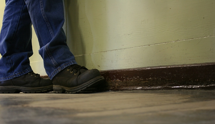A customer steps up to the check out counter, where the wood floor is especially worn.