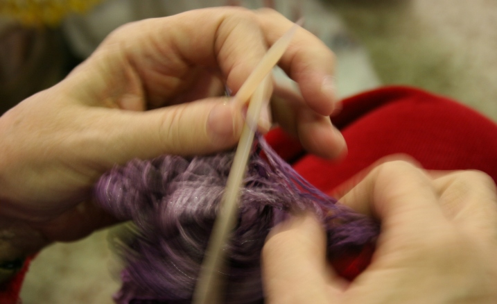 Yarn flies across the needles in Nyla's crafty hands.