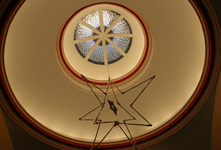 Looking up at a Christmas star suspended from the center stained glass dome.