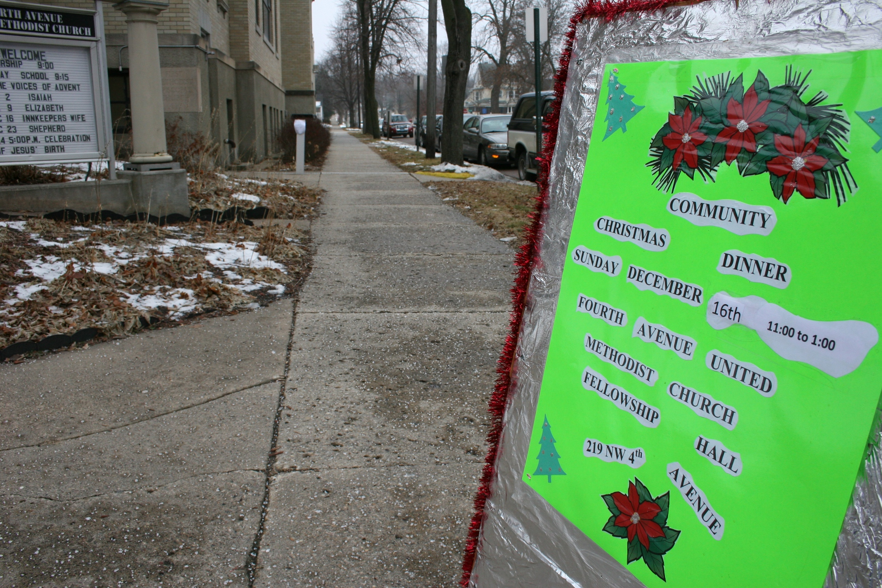 A street-side sign welcomes diners to the free Community Christmas dinner.