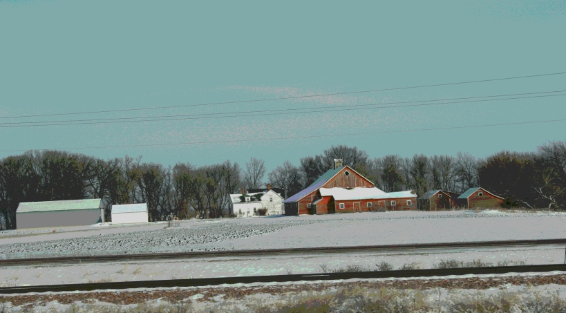 The horizontal lines of railroad tracks and farm buildings define this scene near Janesville along U.S. Highway 14.