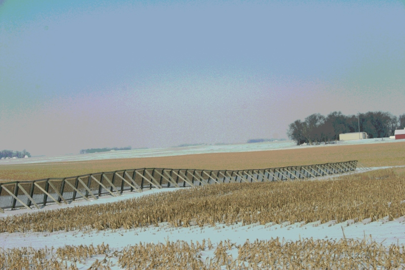 West of Springfield, a snow fence emphasizes the horizontal lines of the prairie.