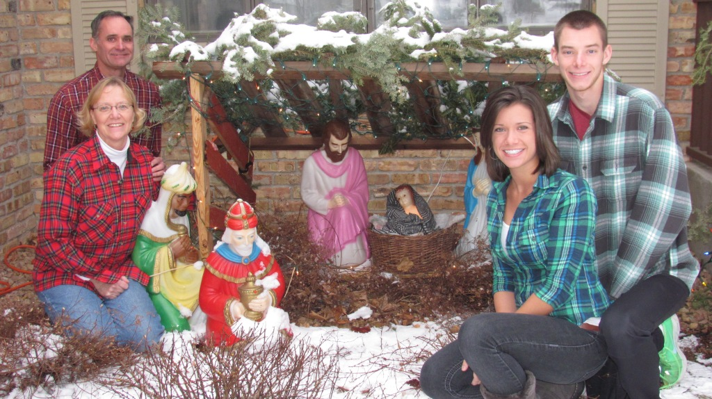 Patrick Mader with his wife, Karen, and children, Karl and Ellen, by the family's nativity set. the wood stable was crafted of wood from the barn on the childhood farm (home of his parents, George and Mary Margaret Mader) near St. Bonifacius where Mader grew up.