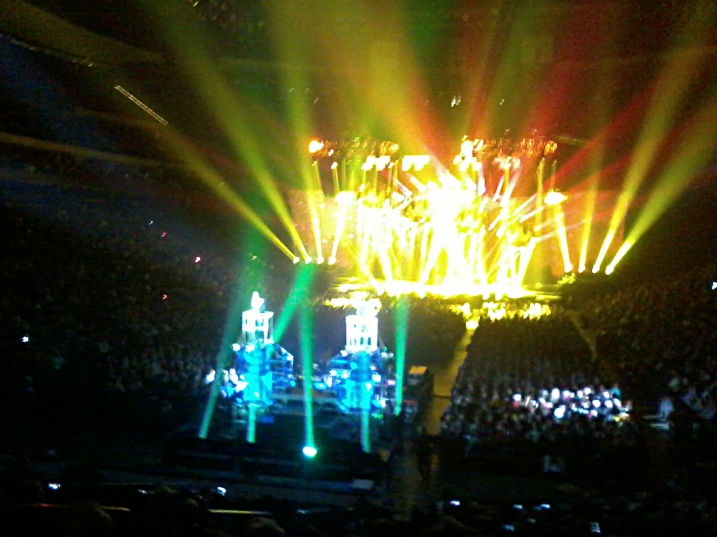 A view of the stage in the background and performers in the foreground elevated onto tiny platforms. I apologize for the horrible images, but DSLR cameras are not allowed into a concert venue and I don't own a compact camera. This image and the second were taken with my cell phone.