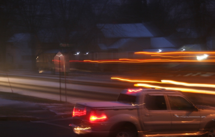The blurred lines of a school bus passing by as a pickup waits on a side street.