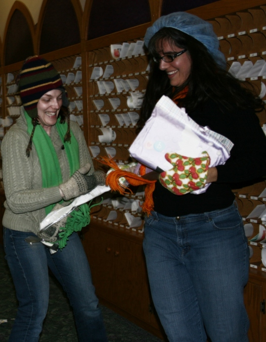 Mandy, left, and Billie Jo vie to open a gift wrapped in multiple layers of boxes and wrapping paper and secured with layers of duct and packaging tape.