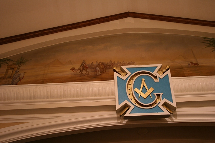 Artwork above an auditorium stage hints at the building's past as a Masonic Temple.