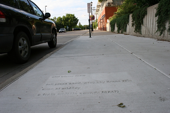 A poem by Patrick Ganey is stamped into the sidewalk near the Northfield Public Library. It reads: still winter thaw  tall pines bend, grey sky drops rain  even at midday  a train whistle sounds lonely