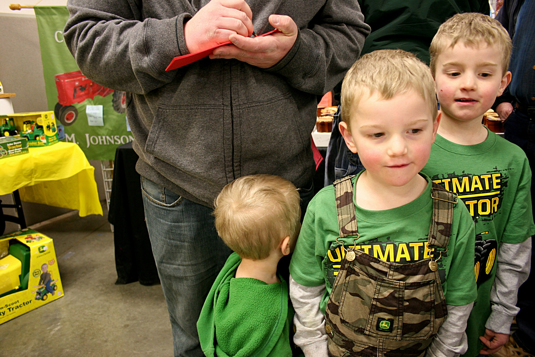 A trio of brothers dressed in John Deere attired waited while their dad signed up for a Massey Harris tractor raffle from Rice County Steam & Gas Engines, Inc.