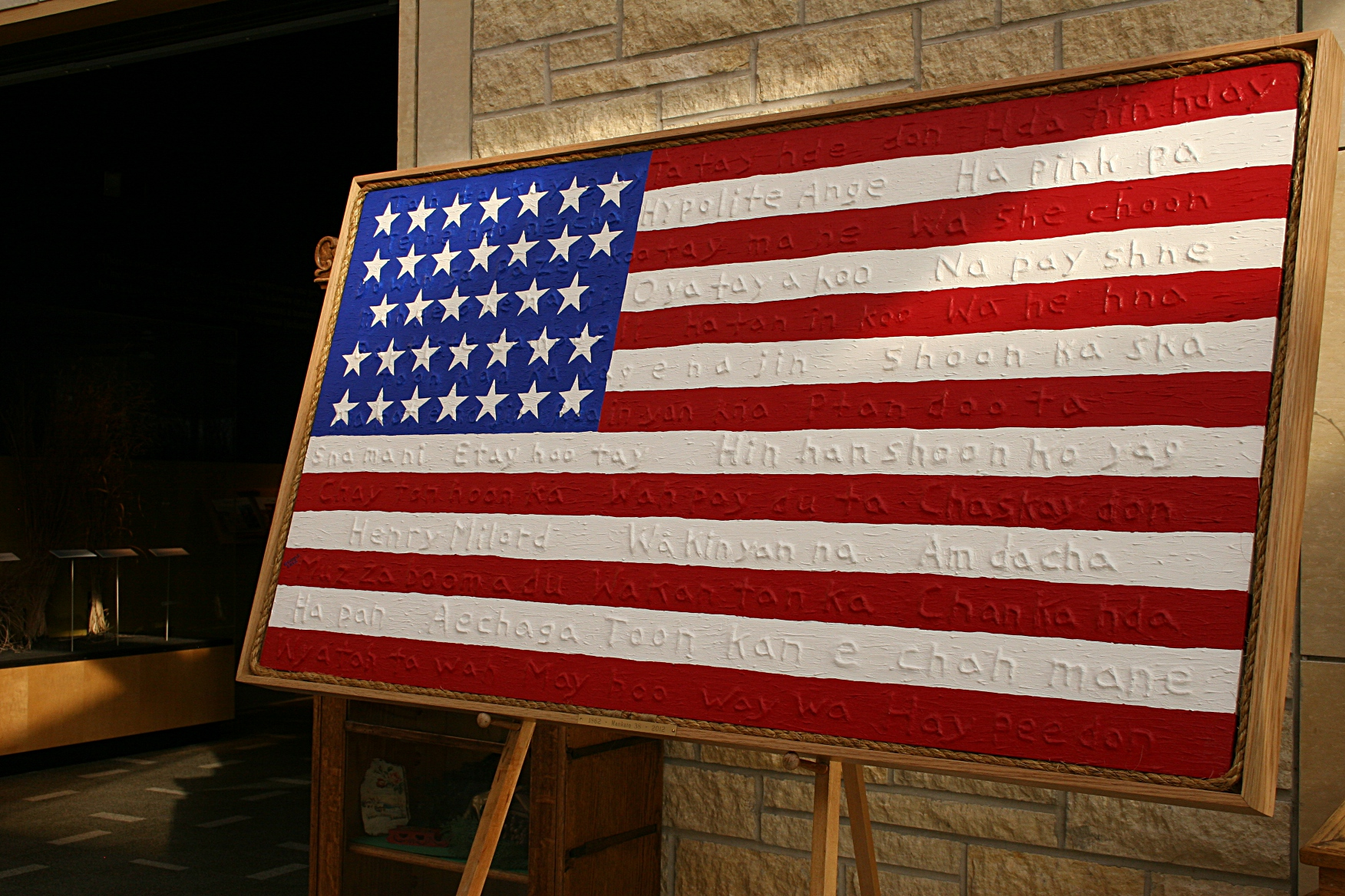 """Gordon M. Coons also created this 1862 U.S. flag which features the names of the 38 Dakota who were executed during a mass hanging in Mankato. """"...the 38 Dakota are woven into the history of the U.S. and appear to be woven into the flag,"""" information posted with the display at the Traverse des Sioux Treaty Center states."""