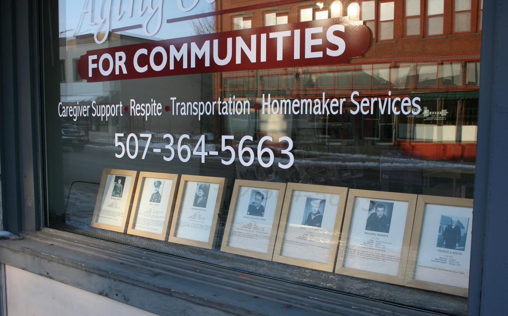 Veterans' photos and information in the window of Aging Services.