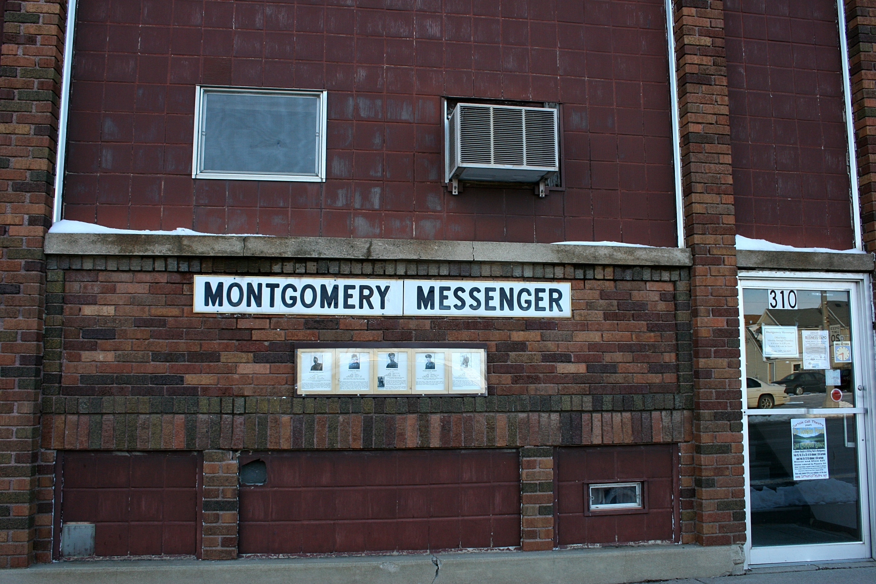 Several vets' photos hang on the exterior of the local newspaper office, The Montgomery Messenger.