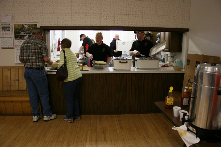 Harlan and Karen step up to the serving window, where Erin, center, and other volunteers dish up food.