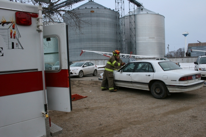 Volunteer firemen remove the windshield from a junk car.