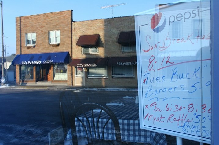 So small town: burgers and a meat raffle promoted on a whiteboard in a restaurant window.