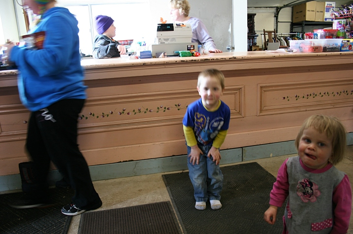 A young customer exits The Store, left, while three of the Thooft kids, including Maxwell, 4, and Beatrice, 21 months, hang out with Mom.
