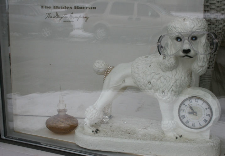 A kitschy poodle clock in a window display.