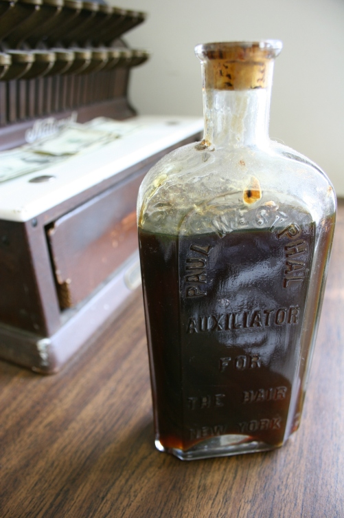"An aged bottle of ""auxiliator for the hair."""