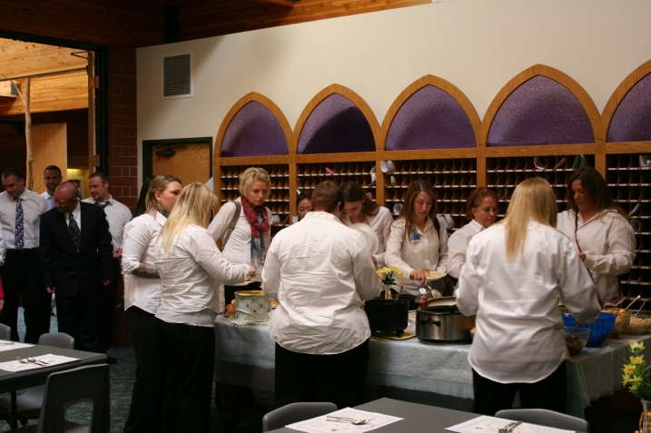 Choir members line up and dish up at the potluck after the service and concert.