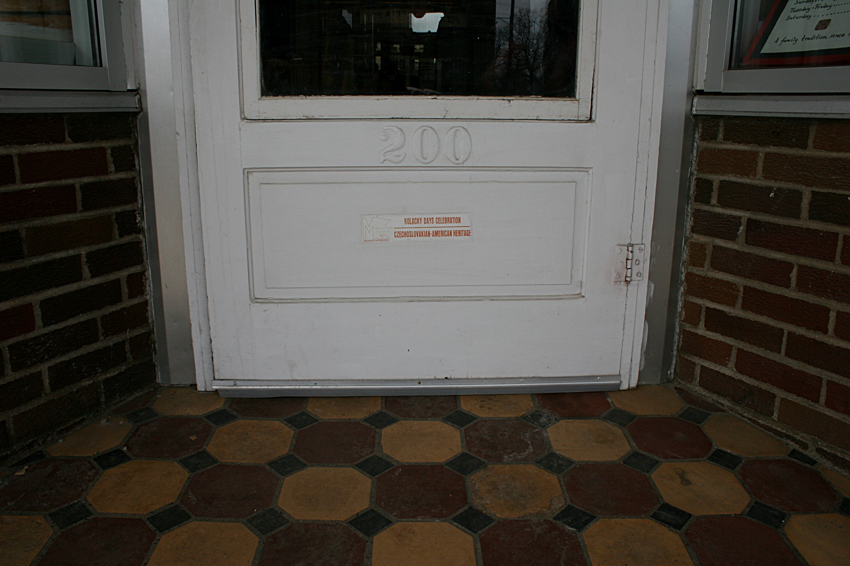 "The tiled exterior entry to Franke's with a sign on the lower part of the door reading: ""Kolacky Days Celebration  Czechoslovakian American Heritage."